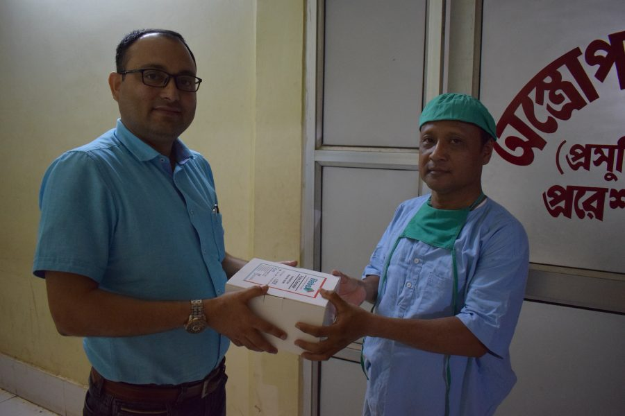 Dr. Giri, left, and a colleague hold the box of a Lifebox pulse oximeter.