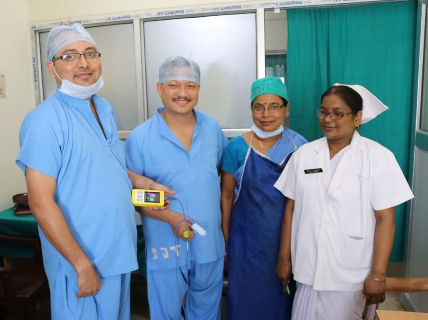 Dr. Giri holds a Lifebox pulse oximeter and stands with his colleagues.