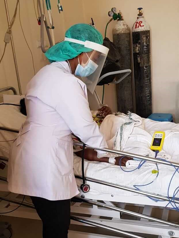 An anesthesiologist tending to a patient at Ghandi Memorial Hospital in Addis Ababa. A yellow Lifebox pulse oximeter is used to monitor the patient.